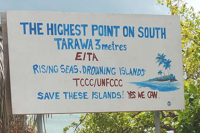 "Hand painted sign calling attention to threat of rising sea level to South Tarawa and plea to ""Save these islands!"""