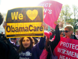 "Woman holding sign: ""We [heart] Obamacare"""