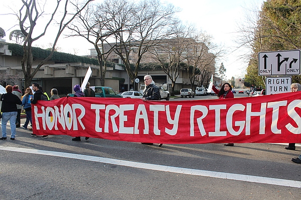 """Group in street holding banner reading """"Honor Treaty Rights"""""""