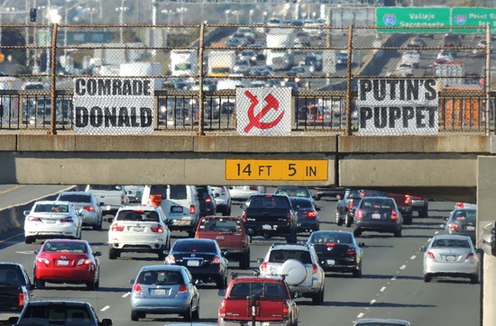 """Comrade Donald"" and ""Putin's Puppet"" signs on freeway overpass"