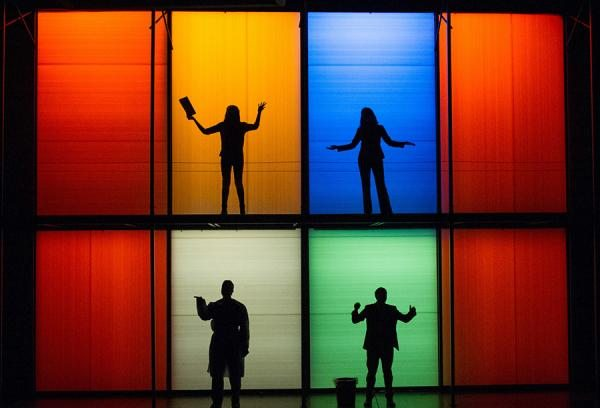 """Stage scene from """"Smart People"""": four actors sillhouetted in boxes back-lit in varied colors"""