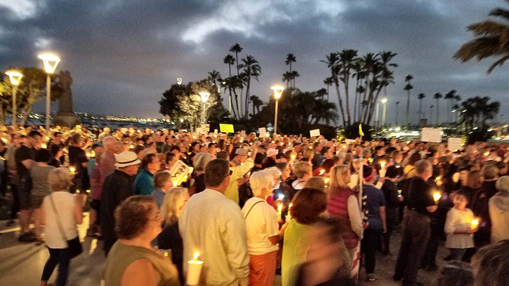 Crowd gathered at dusk, many holding vigil candles